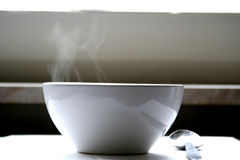 Steaming bowl of soup on table