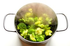 Steaming broccoli in an inox pot. Green vegetable diet , alkaline diet concept . Broccoli is a plant in the cabbage family, whose large flower head is used as royalty free stock images