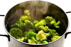 Vegan food : steaming broccoli in an inox pot. Steaming broccoli in an inox pot . green vegetable diet , alkaline diet concept . Broccoli is a plant in the stock images