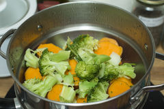 Steaming broccoli and sweet potatoes Stock Images