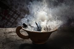 Steaming clay cup with spices on wooden table. Still-life on a background. Nepal. Close up Royalty Free Stock Photo