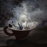 Steaming clay cup with spices on wooden table in street. Still life black background, Nepal. Royalty Free Stock Image