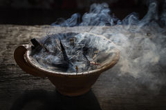 Steaming clay cup with spices on wooden table in street. Still life black background, Nepal. Stock Photo