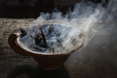 Steaming clay cup with spices on wooden table in street. Still life black background, Nepal. Stock Image