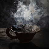 Steaming clay cup with spices on wooden table in street. Still life black background, Nepal. Stock Images