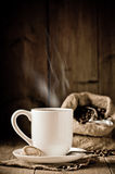 Steaming Coffee. Cup of steaming coffee with biscuits - sack of coffee beans in background stock image