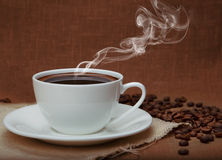 Steaming coffee. On flax background royalty free stock photos