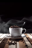 Steaming coffee beans in coffee cup Stock Photography