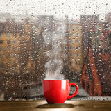 Steaming coffee cup on a rainy day Royalty Free Stock Photos