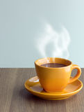 Steaming coffee cup on table Stock Photo