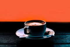 Steaming coffee Latte Art Heart cup on dark with Orange backgrou. Nd Royalty Free Stock Photos