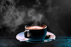 Steaming coffee Latte Art Heart cup on dark with smoke on old wo. Oden background Royalty Free Stock Photo