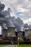 Steaming cooling towers of a power plant with dark gray emission Royalty Free Stock Photography