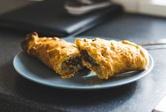 Steaming Cornish Pasty. Cornish pasty cut in half on a blue pastel plate on the kitchen counter Royalty Free Stock Image