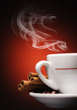 Steaming cup of coffee. Cinnamon sticks and coffee beans royalty free stock photography