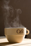 Steaming cup of coffee. On the table royalty free stock photo
