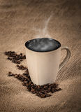 Steaming cup of coffee and coffee beans Stock Images