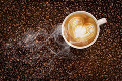 Steaming cup of coffee on coffee beans. Steaming cup of coffee with heart made of frothy milk standing on top of roasted coffee beans Stock Photos