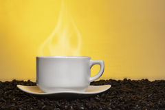 Steaming cup of coffee and coffee beans Royalty Free Stock Images