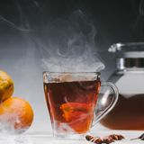 Steaming cup of spicy black tea Stock Photos