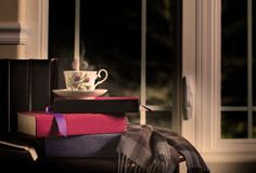 Steaming Cup of Tea and Books. A china cup with Scottish thistle design filled with hot tea that is steaming and resting atop books, dark night through window in stock photos