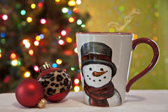 Steaming drink in cheerful mug near a festive Christmas tree. Royalty Free Stock Photo