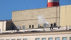Steaming factory pipes. Sunny day 4K pan shot. Clip stock video footage