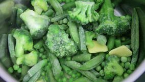 Steaming frozen green vegetables like peas, broccoli and beans stock footage