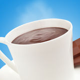 Steaming hot chocolate on blue. Close up of a cup of delicious hot cocoa on blue background Royalty Free Stock Photos