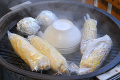 Steaming Hot Corn. Steaming corn and preparing baked potatoes Royalty Free Stock Image