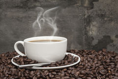 Steaming hot cup of coffee and beans Royalty Free Stock Images