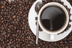 Steaming hot cup of coffee and beans Stock Images