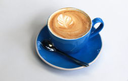 Steaming hot cup of coffee with froth in blue cup Royalty Free Stock Images
