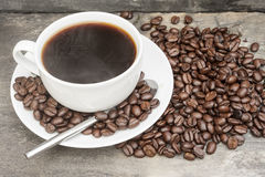 Steaming hot cup of coffee  surrounded by dark coffee beans with Stock Photo