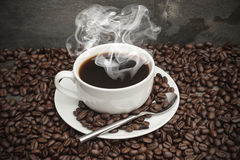 Steaming hot cup of coffee  surrounded by dark coffee beans Stock Photo