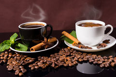 Steaming Hot Cups of Coffee with Roasted Beans. Two Mugs of Steaming Hot Cups of Coffee Garnished with Fresh Mint, Cinnamon Sticks and Star Anise on Black Royalty Free Stock Photography