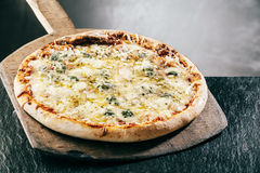 Steaming hot four cheeses Italian pizza. Steaming hot flame grilled four cheeses Italian pizza served on a long-handled wooden board in a pizzeria or restaurant Royalty Free Stock Photo