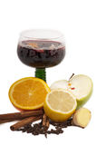 Steaming hot  mulled wine for Christmas. Mulled wine in a green stemmed German wineglass glass surrounded by the ingredients: orange, lemon, cinnamon, cloves Royalty Free Stock Photos