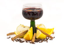 Steaming hot  mulled wine for Christmas. Mulled wine in a green stemmed German wineglass glass surrounded by the ingredients: orange, lemon, cinnamon, cloves Stock Photos