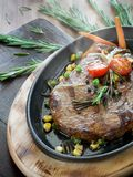 Steaming hot steak in the iron pan Royalty Free Stock Photo