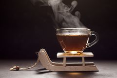 Steaming hot tea glass cup on small wooden sledge. Royalty Free Stock Images