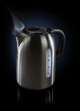 Steaming Kettle. Steaming hot modern electric Kettle with reflections on dark background royalty free stock images