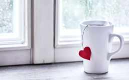 Steaming love heart morning tea mug on window sill Royalty Free Stock Images