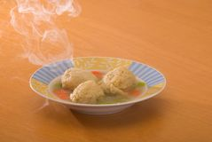 Steaming Matzo Ball Soup. Chicken soup with matzo balls with rising steam; on light wood table Royalty Free Stock Photos