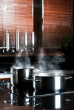 Steaming Metal Cooking Pots. Stainless steel cooking pots with steam on a flat-top stove in a modern kitchen Stock Photography