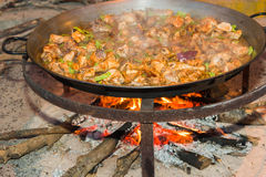 Steaming paella. Steaming classic Spanish paella. Delicious chicken with green bean on the frying pan Stock Image