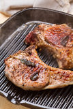 Steaming pork chops on grill frying pan Stock Images