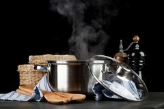 Steaming pot on black background stock photo