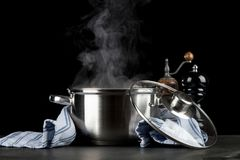 Steaming pot on black background stock photos