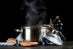 Steaming pot on black background. Steaming pot isolated on black background stock photo